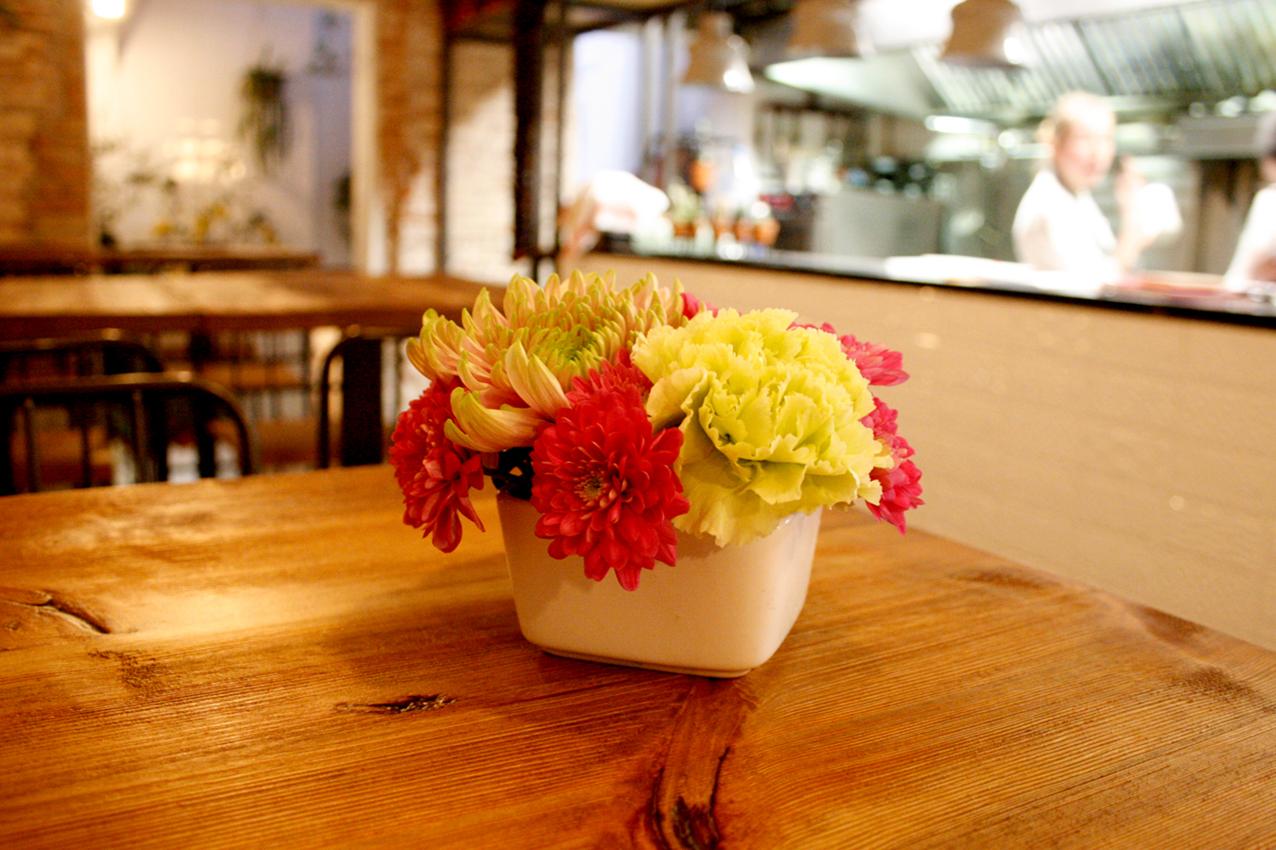 Centre de flores hecho para el restaurante Agust Gastrobar. Centro pequeño de crisantemos uniflora y crisantemos de colores magentas, amarillos y rosas.