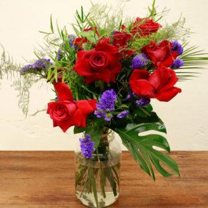 Ramo de flores Guns 'n' Roses con rosas rojas, statice violeta, falcatum, esparraguera plumosa y foxtail fern de colores rojos y violetas.