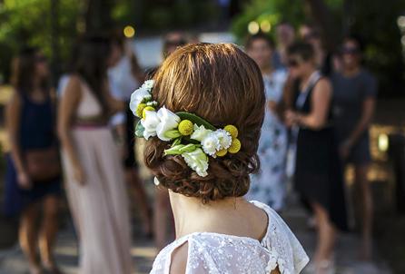 Arranjaments florals per a un casament fresc i mediterrani on vam realitzar la corona pel cap de la núvia, les agulles pel nuvi i el padrí, el ram de la núvia, els centres de taulai la decoració de les cadires de la cerimònia tot amb tons verds, grocs i blancs. Les flors que es van utilitzar van ser els crisantems blancs, lisianthus blancs i craspedies grogues. Vista de la corona del cap de la núvia per darrera. La núvia està d'esquena a l'espectador i observa a les seves amigues.