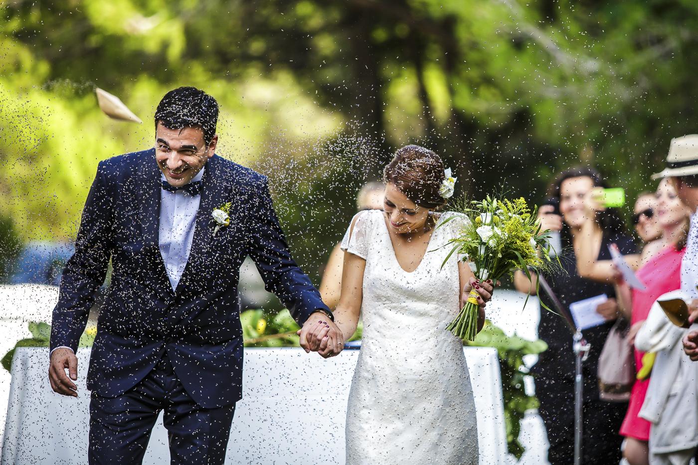 Arranjaments florals per a un casament fresc i mediterrani on vam realitzar la corona pel cap de la núvia, les agulles pel nuvi i el padrí, el ram de la núvia, els centres de taulai la decoració de les cadires de la cerimònia tot amb tons verds, grocs i blancs. Les flors que es van utilitzar van ser els crisantems blancs, solidago lisianthus blancs i craspedies grogues. Vista dels nuvis caminat sota una pluja d'espígol que els convidats els tiren al passar pel passadís on es va fer la cerimònia. S'hi veu l'agulla del nuvi, la corona del cap de la núvia i el ram que agafa amb una mà.