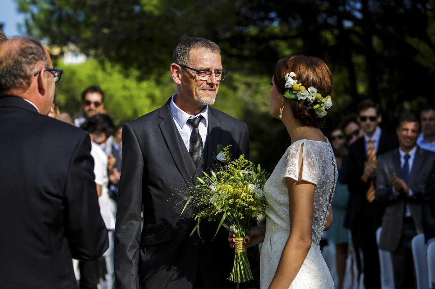 Arranjaments florals per a un casament fresc i mediterrani on vam realitzar la corona pel cap de la núvia, les agulles pel nuvi i el padrí, el ram de la núvia, els centres de taulai la decoració de les cadires de la cerimònia tot amb tons verds, grocs i blancs. Les flors que es van utilitzar van ser els crisantems blancs, lisianthus blancs i craspedies grogues. Vista de la núvia amb la corona i el bouquet amb el seu pare a la cerimònia.