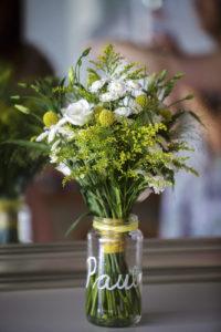 Arranjaments florals per a un casament fresc i mediterrani on vam realitzar la corona pel cap de la núvia, les agulles pel nuvi i el padrí, el ram de la núvia, els centres de taulai la decoració de les cadires de la cerimònia tot amb tons verds, grocs i blancs. Les flors que es van utilitzar van ser els crisantems blancs, lisianthus blancs, solidago i craspedies grogues. Vista del ram de la núvia dins un jetto amb el seu nom. El jerro és un pot de vidre d'aliments reutilitzat.