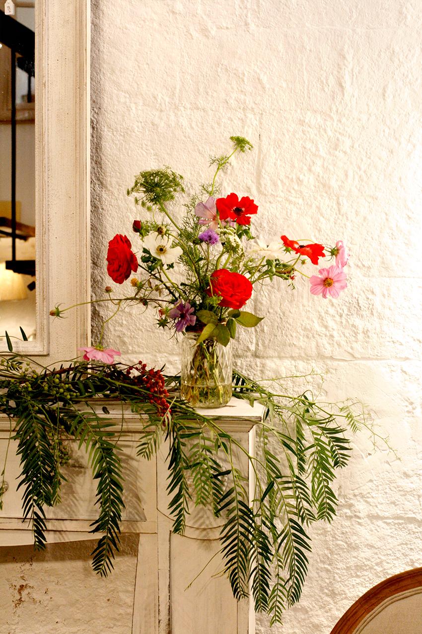 Centre, rams i instal·lació floral per a la botiga de parament de la Llar Lusitània. La peça principal era un arranjament floral d'estil barroc que marcava la línia de disseny de la resta de bouquets i decoracions florals. Instal·lació floral durant la campanya de tardor. Les flors que apareixen en les decoracions són lisianthus, margarites, estromèlies, paniculata, statice, roses de jardí i ortènsies de colors magentes, vermells, granates, violetes i blancs combinades amb verds com ara l'eucaliptus, el fals pebrer o l'ammi majus.