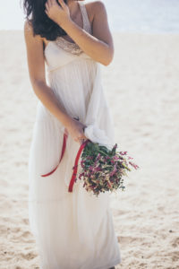 Vista d'un ram o bouquet de núvia inspirat per a un casament a la primavera. Les flors que hi apareixen són diferents tipus de tons de limonium. De colors morats, magentes i blancs barrejats. El ram té un aire silvestre i ferèstec.