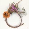 Corona de flor seca. La base és feta d'eucaliptus. Incorpora caluna, limonium i una dàlia taronja